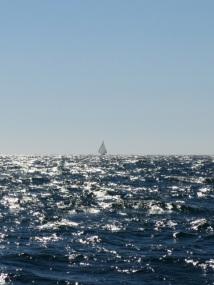 Au loin, un voilier avec ses voiles en ciseaux
